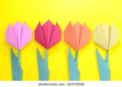 Origami bright colored tulip flowers on a yellow background.