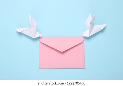 Origami carrier pigeons with envelope on a blue background