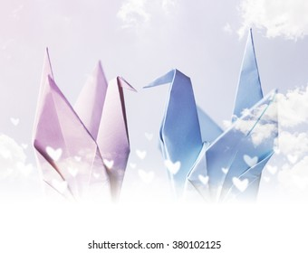 Origami couple paper crane with heart on sky
