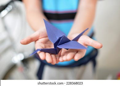 Origami crane in children's hands (soft focused)