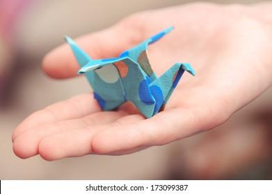 Origami crane on child hand