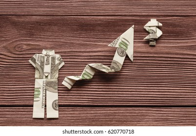 Origami of money dollar banknotes, businessman graph upwards towards dollar symbol, against a background of wooden mahogany boards. Idea: career advancement, business, growth arrived, sales.