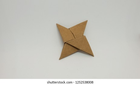 origami ninja star made from brown paper isolated on white background closeup studio