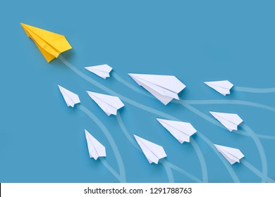 Origami paper airplane in group flying upwards lead by a bigger yellow paper airplane. Conceptual leadership image.