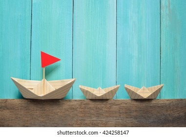 Origami paper boats on a wooden background, summer traveling concept
