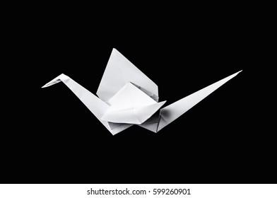 Origami paper crane isolated on black background