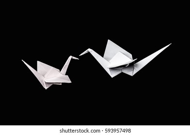 Origami paper cranes isolated on black background