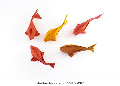 Origami paper red and yellow fishes on white background