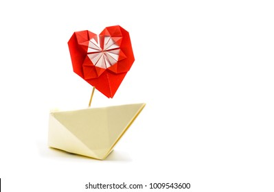origami paper ship with a red paper heart