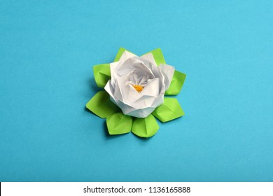 Origami paper water lily white flower on blue background