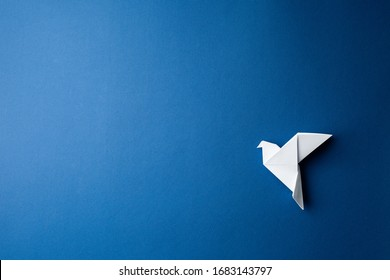 Origami pigeon on a blue isolated background. World Peace Day concept. Close up studio photo.