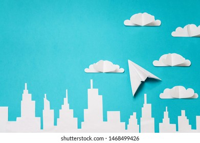 Origami plane and clouds above city silhouette. Craft objects photo for banners/landing pages/backgrounds design.