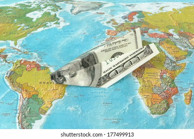 Origami plane made from dollars on the map