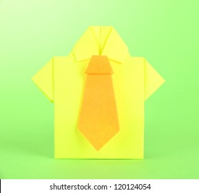 Origami shirt on green background