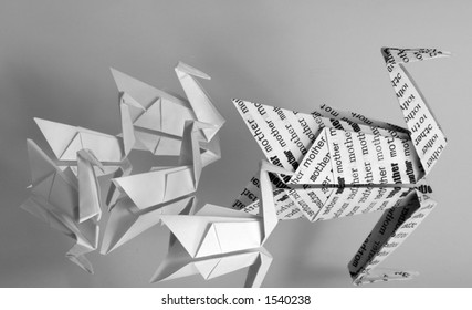 """An origami swan covered with the word """"mother"""" leading a brood of five baby origami swans."""