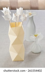 origami tulips in a vase of origami paper on the table with white orchids in a vase