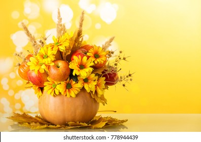 Original autumn bouquet of flowers, fruits and vegetables, decorated with spikelets and spines, in pumpkin, on yellow background