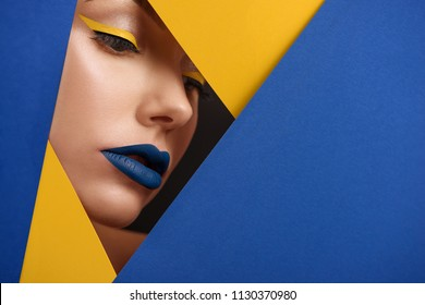Original beaty close up of girl's face surronded by blue and yellow stiff carton sheets. Model having beatiful face, wearing bright make up with yellow eyeliner, blue lipstick. Looking down.