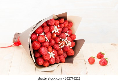 the original bouquet of strawberries with little white flowers on wooden table, light background