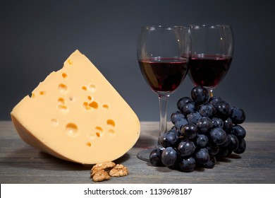 Original composition of gastronomic products. Cheese with a bunch of grapes and two glasses of red wine. Still life on wooden table isolated on gray background