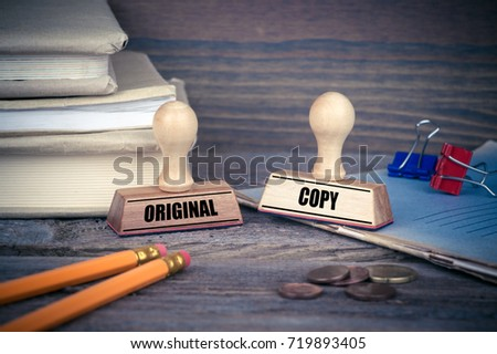 Original and Copy concept. Rubber Stamp on desk in the Office. Business and work background