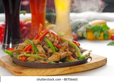 original fajita sizzling smoking hot served on iron plate ,with selection of beer and fresh vegetables on background