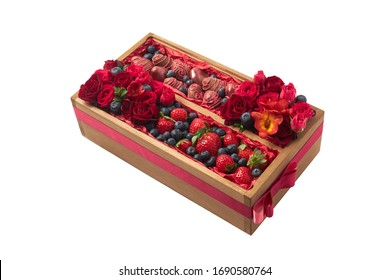 Original gift in the form of a wooden box filled with ripe chocolate covered strawberries, blueberries and red flowers on a white background