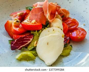 Original hamon, cherry tomato, strawberry and mozzarella salad on a blue plate.