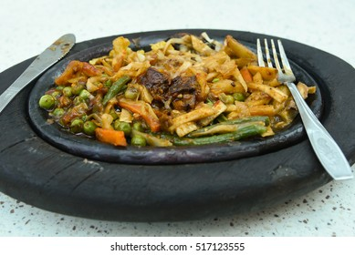 Original hot and spicy chicken sizzler/fajita served on wood/sizziling plate, Mumbai India. Indian spices used. Sweet and sour lean meat with vegetables and sauce.