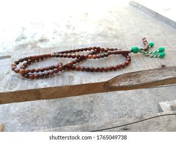 Original kokka wood prayer beads, Muslim prayer beads lying on the ceramic surface