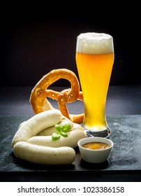 Original Munich sausage with Hefeweizen and pretzel on black slate plate