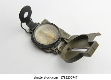 Original old army compass. Used compass with signs of use. Olive army compass on white background. Soldier equipment. Outdoor equipment.