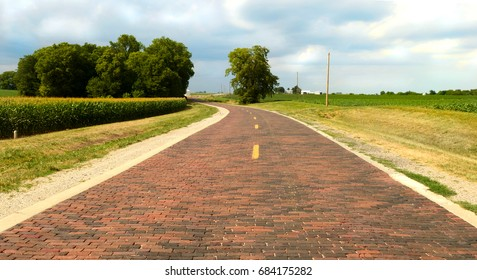 Original section of Route 66 which is 1.4 miles of hand-lain brick road and was completed in 1931. The road curves through the corn fields near Auburn, Illinois.