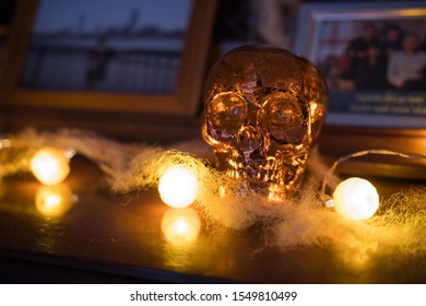 Original shiny skull on a wooden furniture. Beautiful close up of this unusual object surrounded by orange fairy lights. Scary halloween decoration, October 31. Low light and blurred background.
