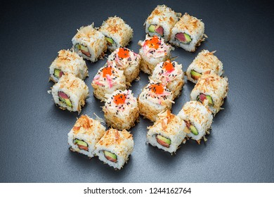 Original sushi roll set with salmon and avocado served on a dark background, close up shot isolated