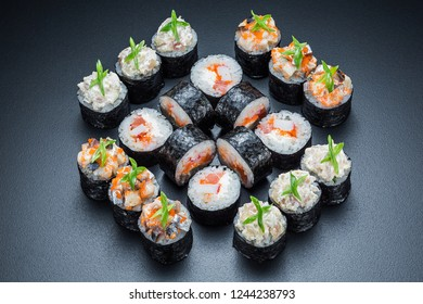 Original sushi roll set with salmon and caviar close up isolated on a dark background