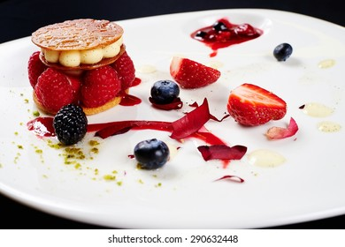Original unusual berry dessert with honey tuille, raspberry and cream, decorated with strawberries, blueberries, cream, BlackBerry, jam with berries, rose petals on a white plate on a black background
