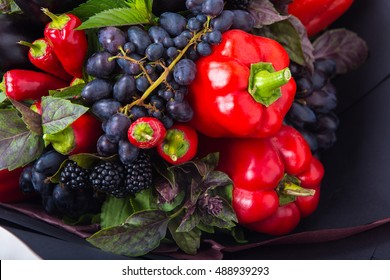 The original unusual edible bouquet of vegetables and fruits on which there is a sweet and hot peppers, and grapes
