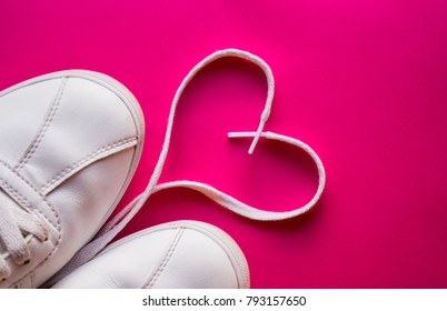 Original Valentine's Day love concept. white sneakers  on a pink background