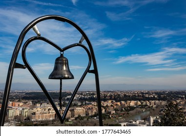 original view over Rome, Zodiaco, monte Mario; bell inside the shape of a metal heart through which emerges the view of the city; urbanization and buildings seen from above, romantic observatory; love