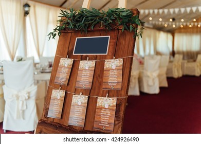 Original vintage wooden board with decoration and ribbons and a guest list, heart and bucket in the background. with a place for an inscription