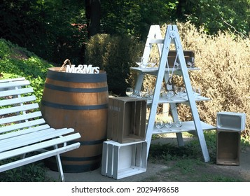 Original wedding bar in the shadowy garden.  Ladder, barrel, benchand wooden boxes as romantic rural furniture prepared for party.