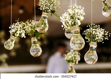 Photo of Original wedding floral decoration in the form of mini-vases and bouquets of flowers hanging from the ceiling