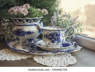Original white porcelain dishes, a vase for sweets with handles in the shape of butterflies with a bouquet of pink chrysanthemums and a pair of tea painted with blue roses in the national Russian styl - Shutterstock ID 1944481759