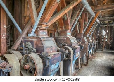 Original wooden belt driven grist mill equipment inside turn of the century factory.