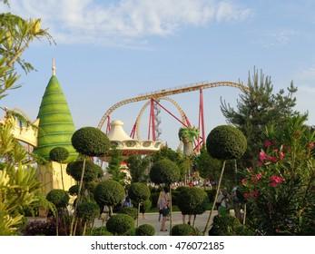 Originally trimmed trees, flowering oleander, people walking in the amusement park, Sochi, Russia, June 1, 2016