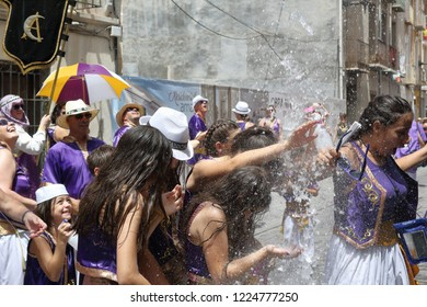 Orihuela, Spain - January 01, 1970: People under a water jet from Moros Almohabenos company on a street parade during the Moors and Christians historical reenactment in Orihuela, Spain