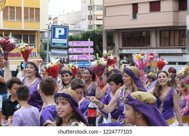 Orihuela, Spain - July 15, 2018: The Moros Almohabenos company women with flowers on a street parade during the Moors and Christians historical reenactment in Orihuela, Spain