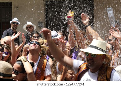 Orihuela, Spain - July 17, 2018: People under a water jet from Moros Almohabenos company on a street parade during the Moors and Christians historical reenactment in Orihuela, Spain