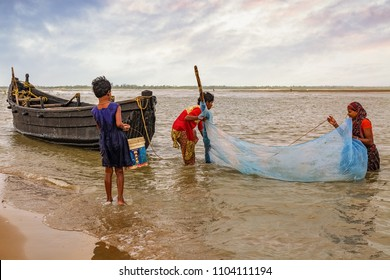 Orissa, India, May 30,2018: Rural Indian women fishing with nets at sea with view of wooden fishing boats at the coastal area of Orissa India.